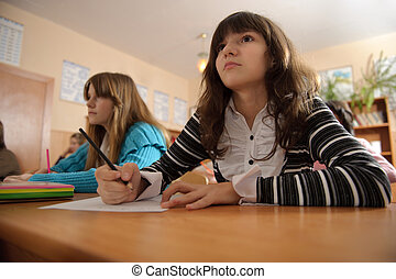 Attentive schoolgirl is listening to her teacher during lesson