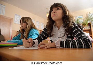 Attentive schoolgirl is listening to her teacher during...