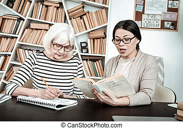 Attentive senior female person writing dictation seriously -...
