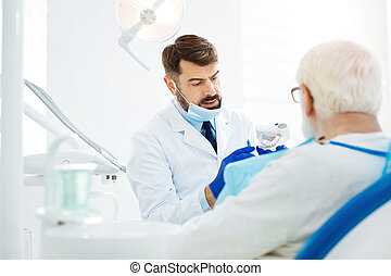 Attentive stomatologist holding false teeth in hands