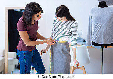Attentive tailor measuring the waist of a very slim woman