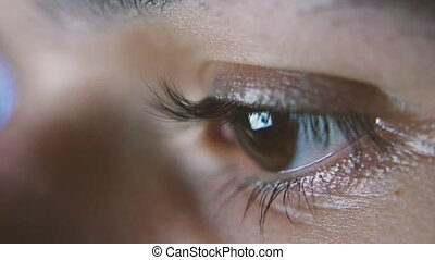 Attentive woman`s eye with long eyelashes looking and...