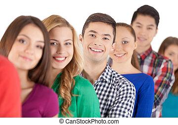 attesa, in, linea., giovani persone, standing, fila, e, sorridente, macchina fotografica, mentre, isolato, bianco