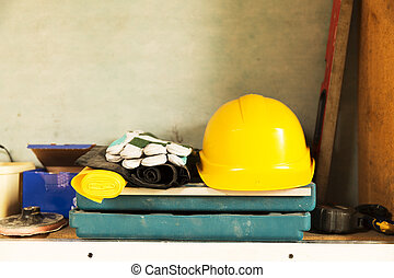 Attic construction and renovation tools, yellow safety helmet, gloves, tool box, measuring tape and other tools.