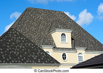 Attic window on the gray tile roof