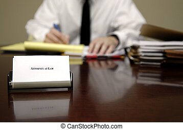 Attorney at Desk - Attorney at Law sitting at desk holding...