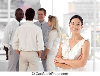 attracive, e, confiante, mulher negócio, frente, um, grupo, de, sócios, sorrindo