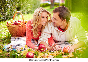 Happy young couple with ripe apples looking at one another while having rest in park
