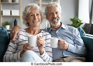 Attractive 60s spouses holding coffee cups smiling looking ...
