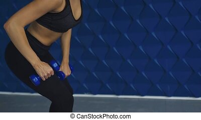 Attractive adult fitness woman performing lunges with dumbbells in the gym