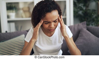Attractive African American girl is suffering from headache...