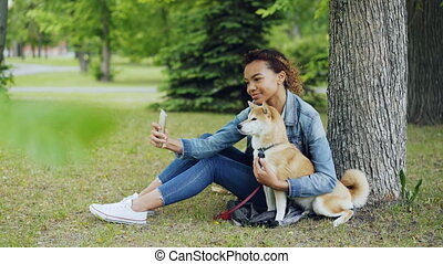 Attractive African American girl is taking selfie with cute...