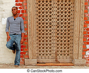 Attractive African American male standing by a doorway