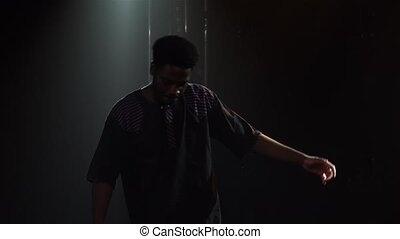 Attractive African American man dancing folk ethnic dance in a dark studio against the backdrop of bright lights. Black man dancing barefoot. African folklore. Close up