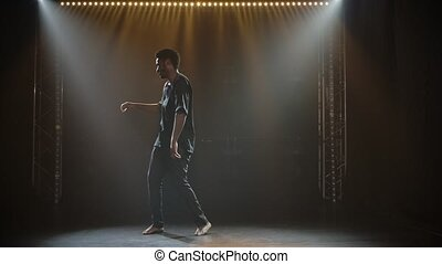 Attractive African American man dancing folk ethnic dance in a dark studio with backlight. Black man dancing barefoot. African folklore. Slow motion