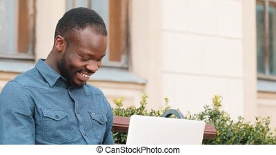 Attractive African American man working on laptop computer sits on the bench. Received good news excited and happy. Remote freelance work. Success concept