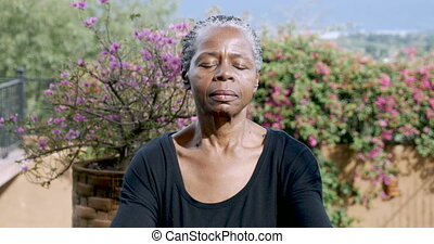 Attractive African American senior woman meditating outdoors...