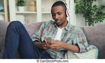 Attractive African American student is using smartphone...