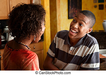 African-American woman and teen laugh in kitchen - ...