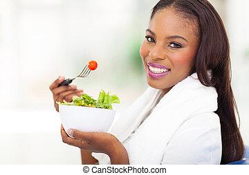 african american woman eating fresh green salad