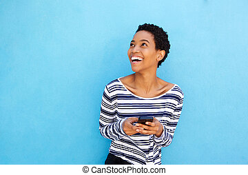 attractive african american woman holding cellphone by blue wall