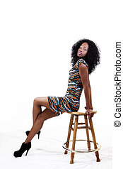 Attractive African American Woman In Dress On Stool