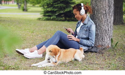 Attractive African American woman is listening to music with...