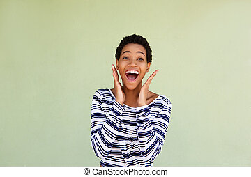 attractive african american woman laughing against green wall