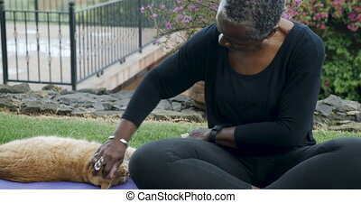 Attractive African American woman playing with her frisky pet orange cat