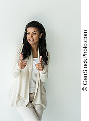 attractive african american woman showing thumbs up on white