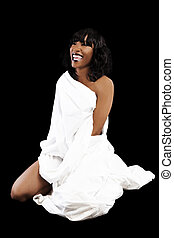 Attractive African American Woman Sitting Against Black Background