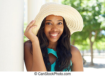 Attractive african american woman smiling with sun hat