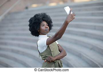 Attractive african american woman taking a picture of herself with her camera phone on a amphitheatre stairs