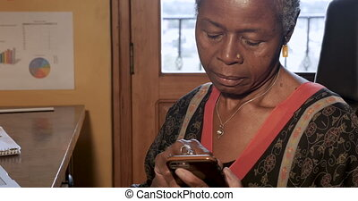 Attractive African American woman using her smart phone...