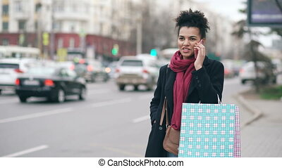 Attractive african american woman with shopping bags talking...