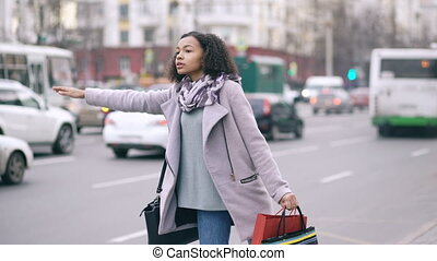 Attractive african american woman with shopping bags calling...