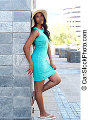 Attractive african model leaning against wall in a dress