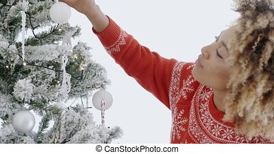Attractive African woman decorating an Xmas tree with themed...