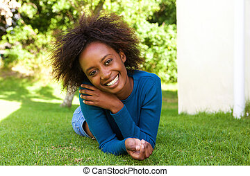 Attractive african woman lying on grass smiling