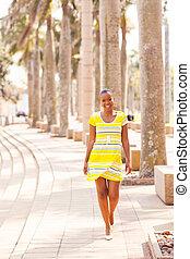 african woman walking down the urban street