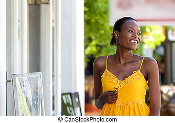 Attractive african woman walking outdoors with flower