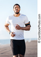 Attractive african young sportsman running outdoors in the...
