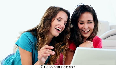 Attractive amused women using notebook lying on floor in...