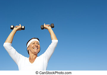 Attractive and active senior woman exercising with weights,  isolated with blue sky as background and copy space.