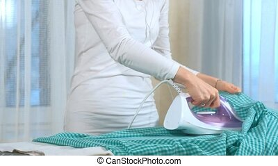 Attractive and beautiful woman ironing clothes at home