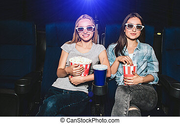 Attractive and charming girls are sitting in chairs in cinema. Each of them has a different size of baskets with popcorn. Brunette is eating popcorn while blonde girl is posing and looking straight.