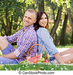 Attractive and cheerful couple staying eating fruits in a park