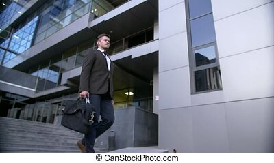 Attractive and confident businessman walking near modern office building