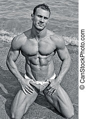 Attractive and fit young bodybuilder in bathing suit kneeling on the beach, black and white shot