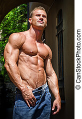 Attractive and muscular male bodybuilder shirtless in jeans...